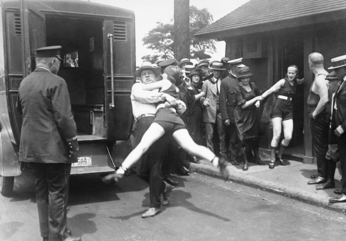 "July 12, 1922 In Chicago, Illinois, a woman is being arrested for defying a Chicago edict banning ""abbreviated bathing suits"" on beaches. Image: Bettmann/CORBIS"
