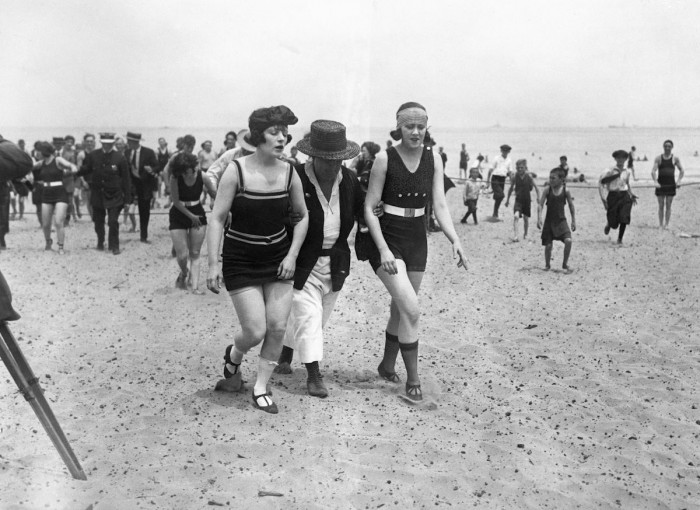 April 1922 Chicago, Illinois - Two bathers being escorted off the beach by a police woman.