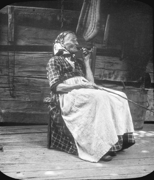 Old woman smoking a pipe, Appalachia, USA, c1917. Photograph taken during Cecil Sharp's folk music collecting expedition: British musician Sharp (1859-1924) and his assistant Dr Maud Karpeles (1885-1976) collected folk songs from the mountain singers of the Appalachians (North Carolina, Tennessee, Virginia, West Virginia, and Kentucky), between 1916 and 1918.  (Photo by EFD SS/Heritage Images/Getty Images)