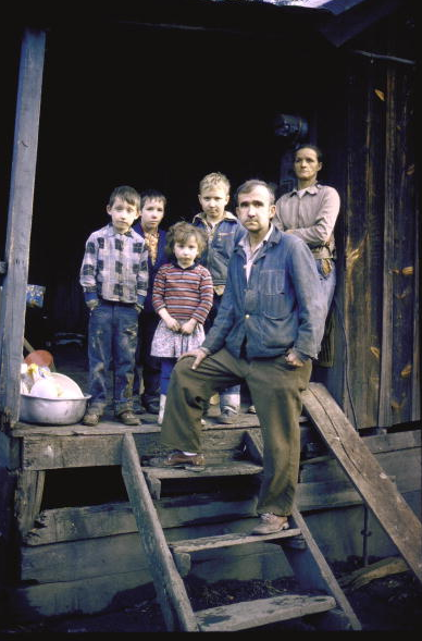 Unemployed miner standing w. his family, who live on Social Security, on porch or their small home re: poverty in Appalachia. 1964