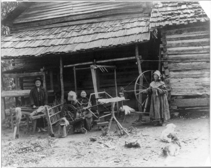 Mary Faust standing next to large walking wheel, an umbrella swift, another woman seated at a spinning wheel with a distaff and a skein winder in front of her, and a man processing flax on a flax break with a counterbalance loom behind him.