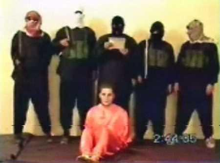 """Nick Berg seated, with five men standing over him. The man directly behind him, said to be Zarqawi, is the one who beheaded Berg.""https://en.wikipedia.org/wiki/Nick_Berg"