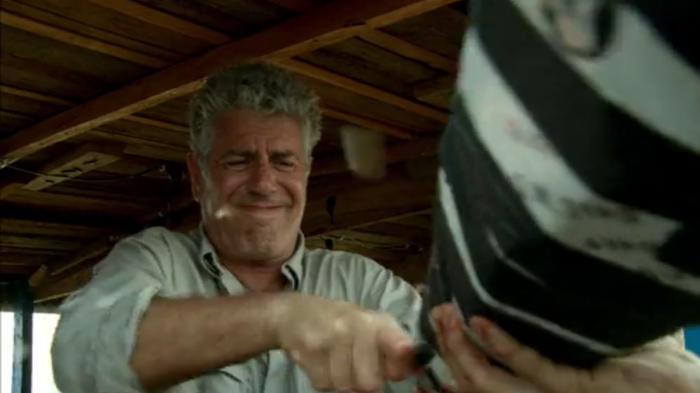 Bourdain haphazardly killing a chicken while crossing the Congo during Parts Unknown, screenshot by the author.
