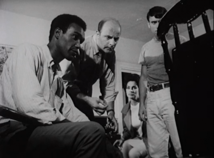 Survivors gather around a television screen, watching broadcast news media of the 1960s during the Night of the Living Dead, screenshot by the author.