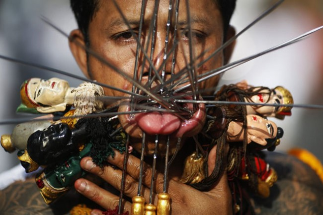 A devotee of the Chinese Kathu shrine with his face pierced takes part in a procession during the annual vegetarian festival in central Phuket
