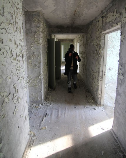 A Ukranian government escort walks in a corridor on the seventh floor of Hotel Pripyat