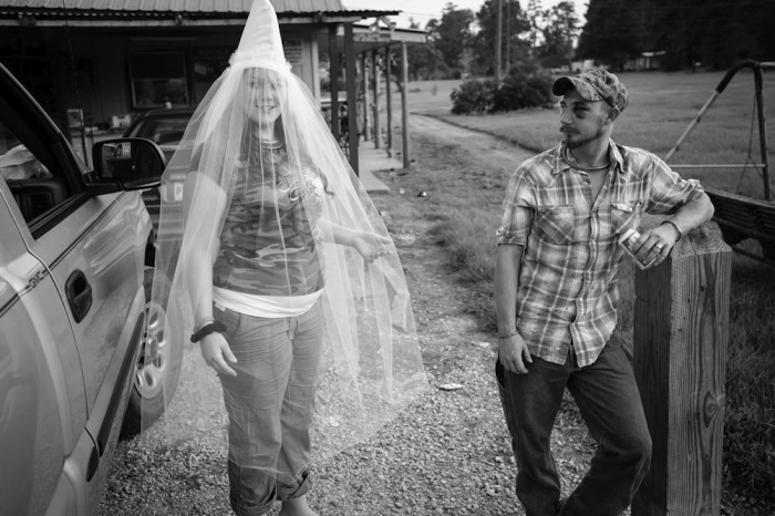 """""""Little Charlie"""" poses in her custom made Klan wedding veil, as her fiancé watches on. I was told the black eye was from a work related accident."""