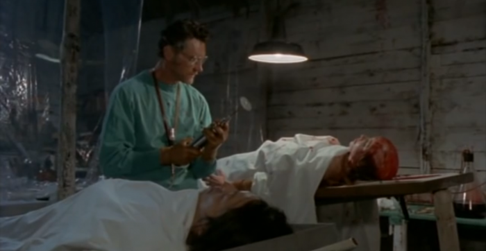 A mad scientist performs a brain transplant from the living to the dead, in Zombie Holocaust, screenshot by the author.
