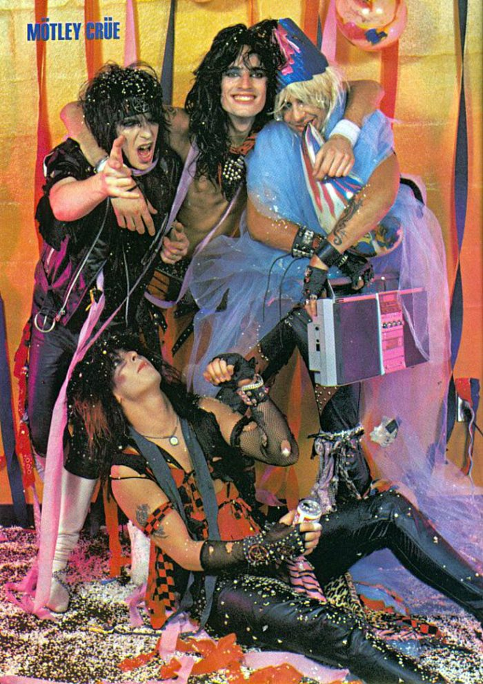 Nothing says hair metal more than wearing a pentagram headband while being hugged by a glitter-wielding, tutu-wearing fellow band member.